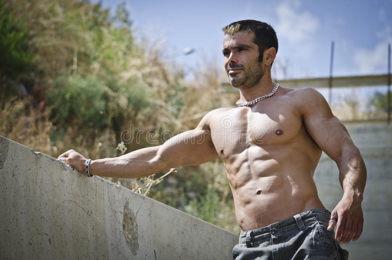 Muscle man shirtless outdoors, concrete wall stock image