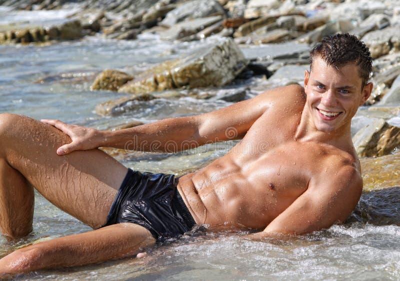 Muscle o homem despido 'sexy' do sorriso molhado que encontra-se na água de mar foto de stock royalty free