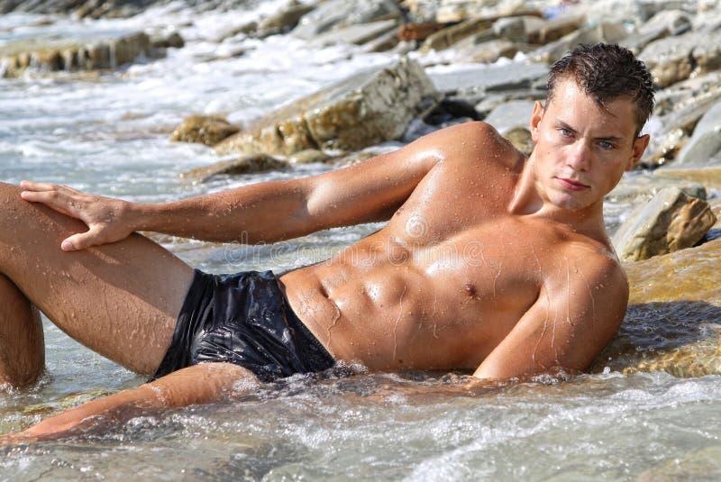 Muscle o homem despido 'sexy' molhado que encontra-se na água de mar imagens de stock