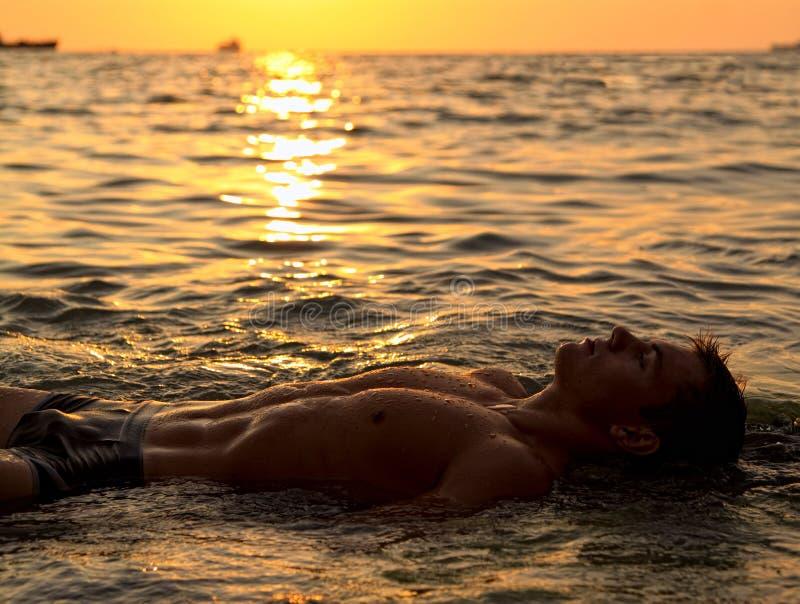 Muscle o homem despido 'sexy' molhado que encontra-se na água de mar imagem de stock