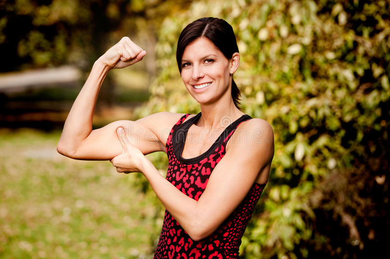 Muscle Woman. A woman flexing her biscep and making it larger stock image