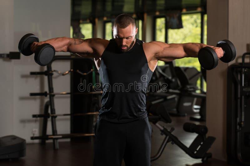 Muscled αρσενικό πρότυπο που ασκεί τους ώμους με τους αλτήρες στοκ εικόνες