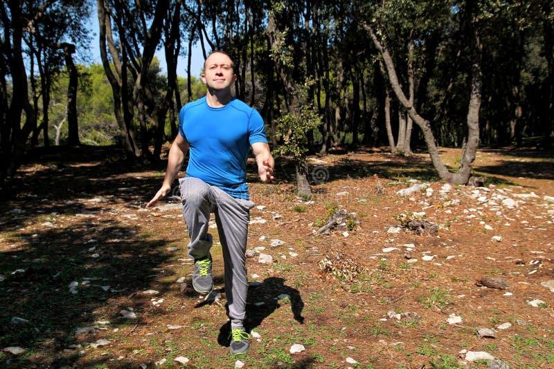 Muscled человек делая тренировку побежали разминкой, который на месте в sportswear красивого спортсмена леса нося бежит на месте  стоковое изображение rf