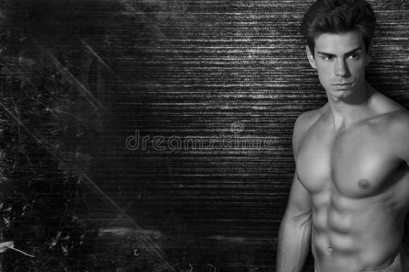 Muscled handsome italian boy on dark vintage background. On side free space. Black and white stock photography