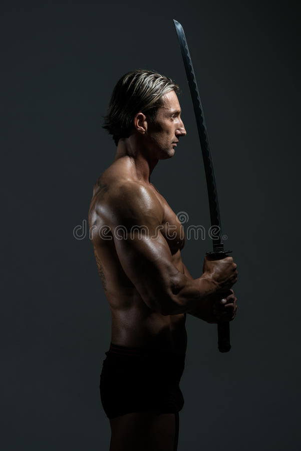 Muscled Male Model In Studio With A Sword royalty free stock photo