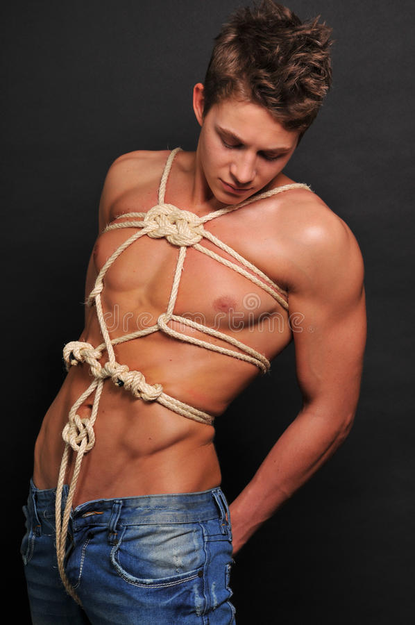 Muscled man bound with rope royalty free stock photo