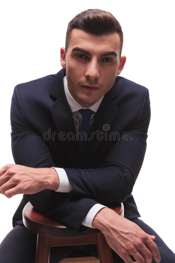 Muscled man in suit with resting hands crossed stock photos