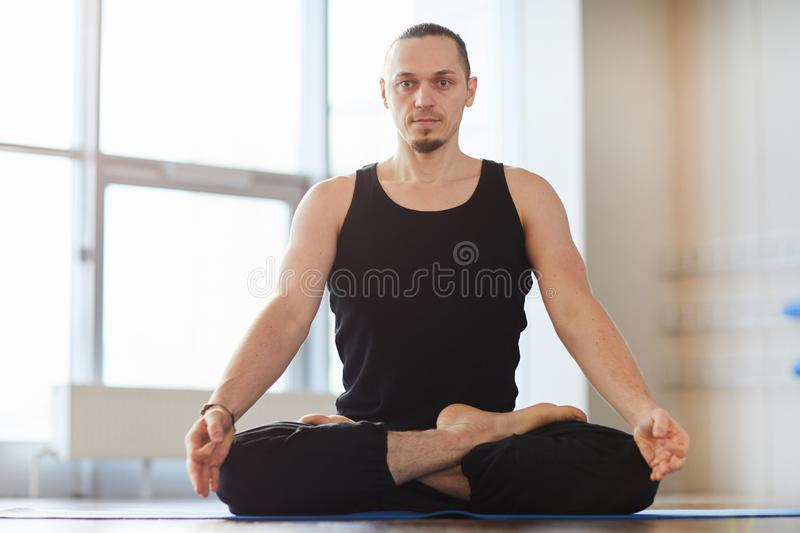 Muscled young man meditating alone stock image