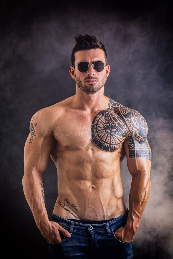 Muscleman descamisado atractivo en fondo oscuro foto de archivo