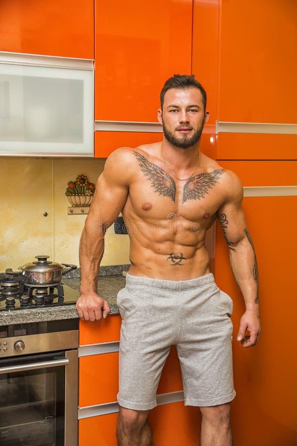 Muscleman farpado 'sexy' na cozinha fotos de stock royalty free