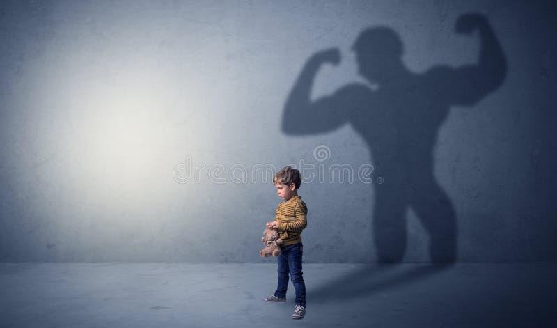 Musclemanschatten hinter schelmischem kleinem Jungen lizenzfreie stockfotos