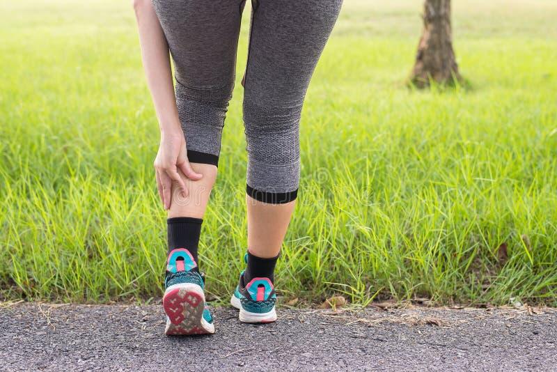 Muscolo del vitello nel dolore con il crampo, la donna che soffrono dal dolore nella lesione di gamba dopo il funzionamento di es fotografie stock