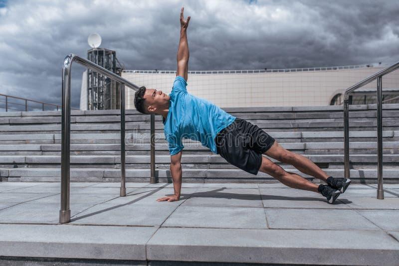 Muscolo maschio che allunga, addestramento di forma fisica, yoga di pratica della città di estate dell'atleta dell'uomo attraente fotografia stock libera da diritti