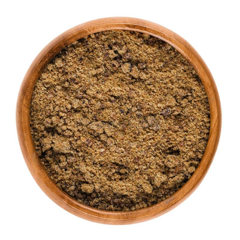 Muscovado brown cukier w drewnianym pucharze nad bielem fotografia stock