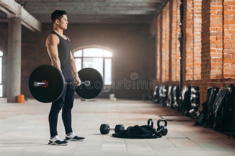 Muscular active sportsman holding barbell in gym stock photography