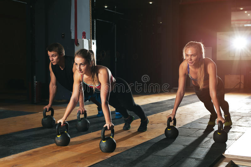 Muscular adults exercising with kettle bell in gym royalty free stock photos
