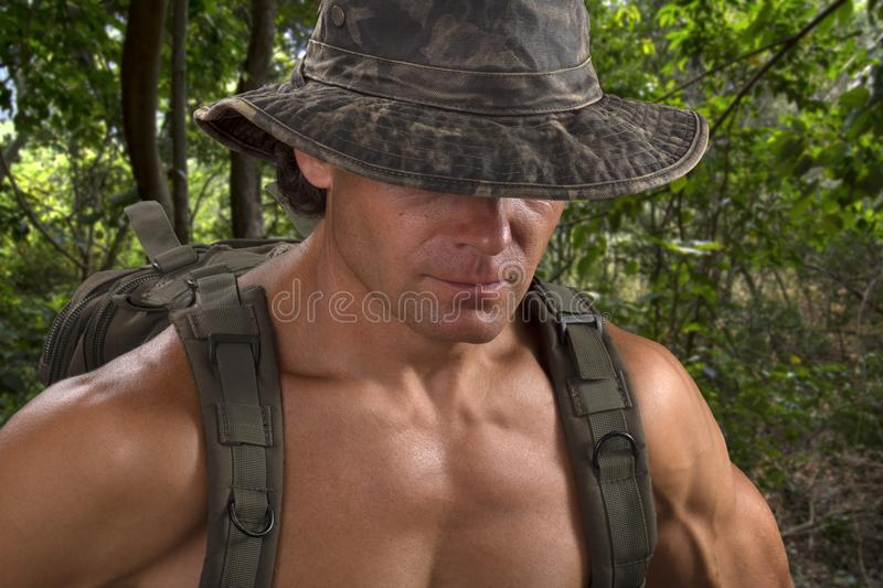 Muscular adventure man in camo hat hiking in jungle royalty free stock images