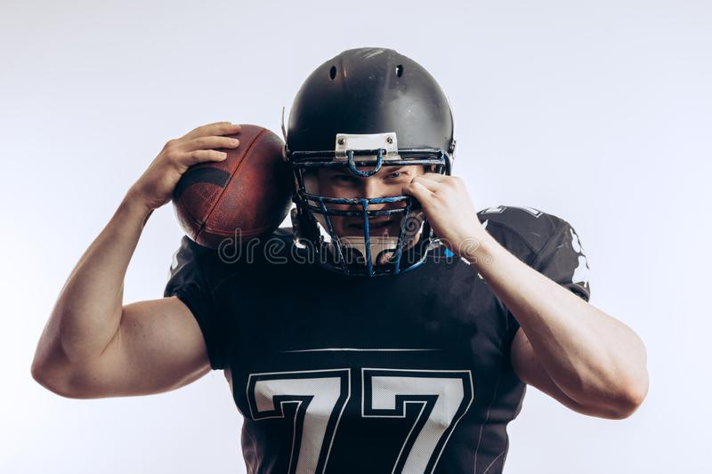 Muscular american football player in protective uniform and helmet holding ball. Muscular american football player in uniform and helmet holding ball, ready to stock photography