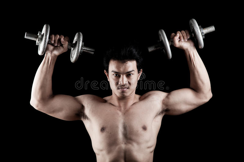 Muscular Asian man with dumbbell stock photo