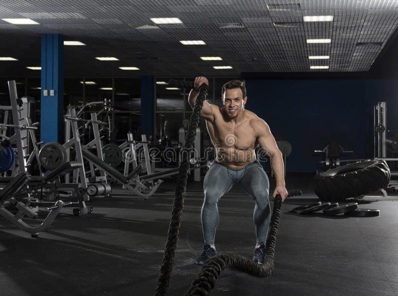Muscular athlete with battle ropes exercise in modern fitness ce stock photos