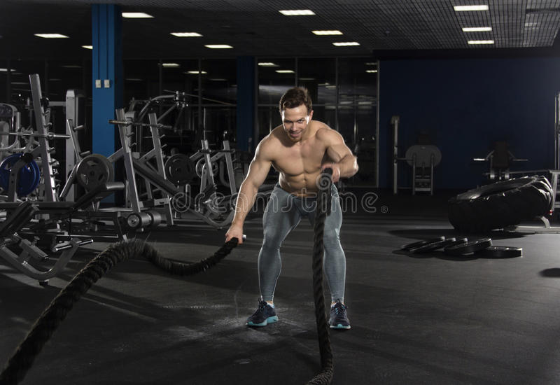 Muscular athlete with battle ropes exercise in modern fitness ce royalty free stock photo