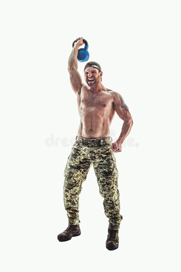 Muscular athlete bodybuilder man in camouflage pants with a naked torso doing Fitness Kettlebells swing exercise on a royalty free stock photography