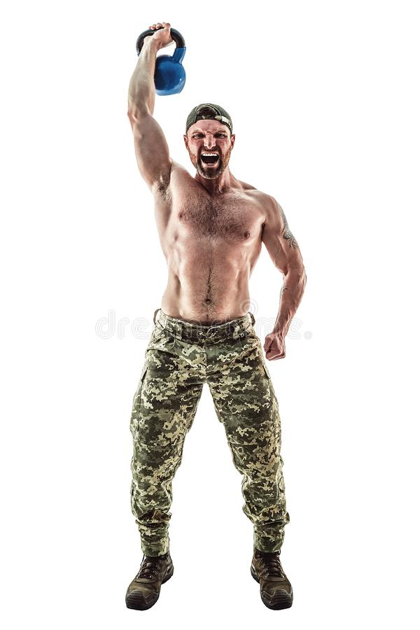 Muscular athlete bodybuilder man in camouflage pants with a naked torso doing Fitness Kettlebells swing exercise on a stock photography