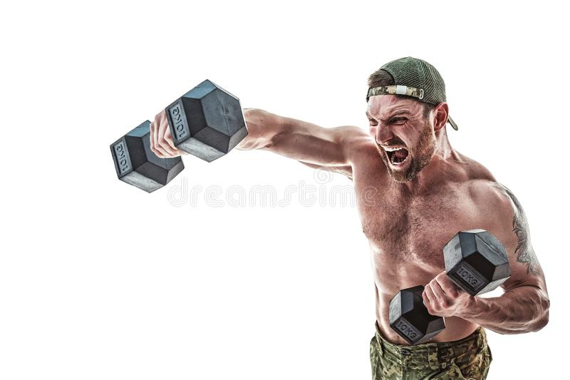 Muscular athlete bodybuilder man in camouflage pants with a naked torso punching with dumbbells like boxer on a white stock photography