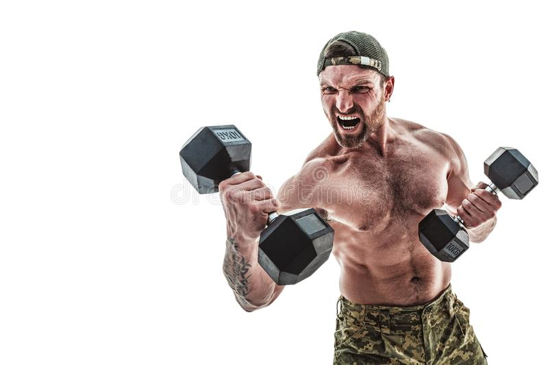 Muscular athlete bodybuilder man in camouflage pants with a naked torso punching with dumbbells like boxer on a white stock photos