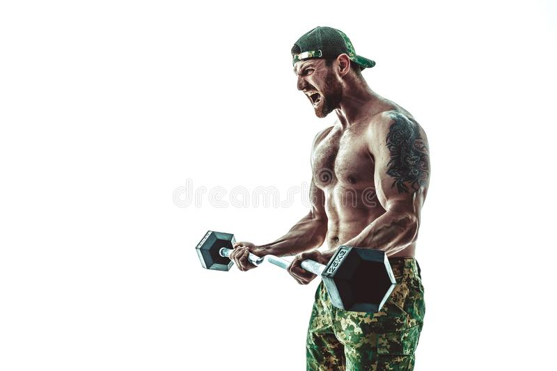 Muscular athlete bodybuilder man in camouflage pants with a naked torso workout with dumbbell on a white background. stock photo