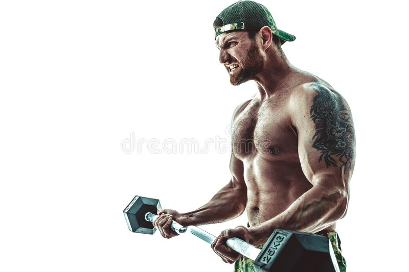 Muscular athlete bodybuilder man in camouflage pants with a naked torso workout with dumbbell on a white background. stock image