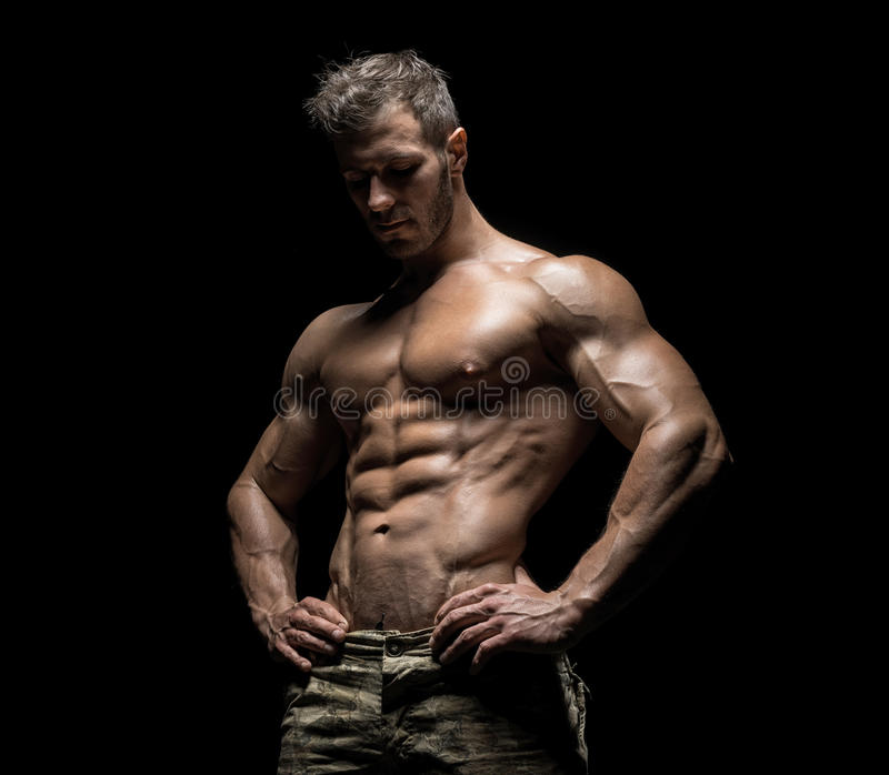 Muscular athlete bodybuilder man on a dark background. Muscular athlete bodybuilder man in camouflage pants with a naked torso on a dark background royalty free stock images