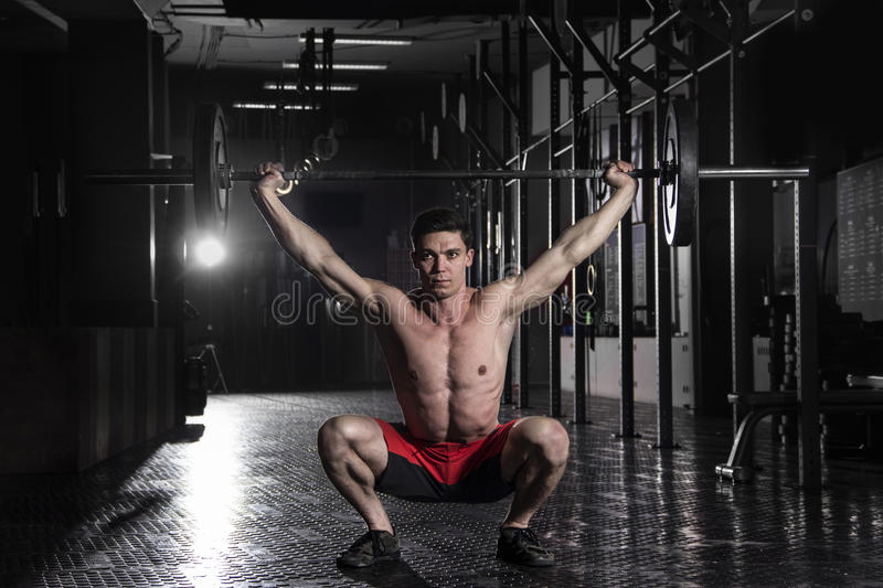 Muscular athlete doing the crossfit exerise in the gym.Doing the stock photography