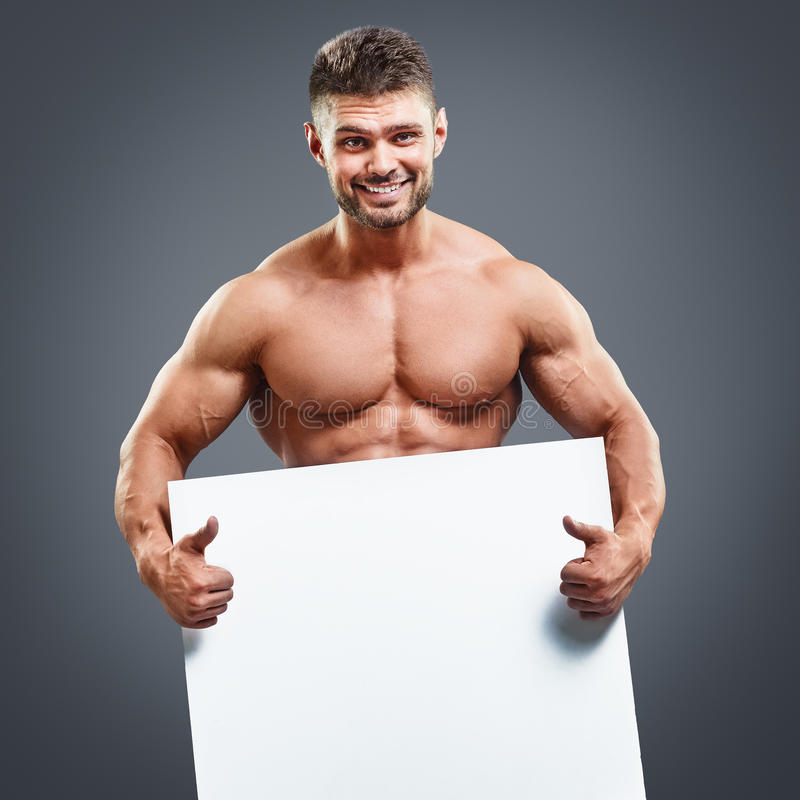 Muscular athlete holding blank white poster. On gray background. Fitness man holding white board in hands royalty free stock photography