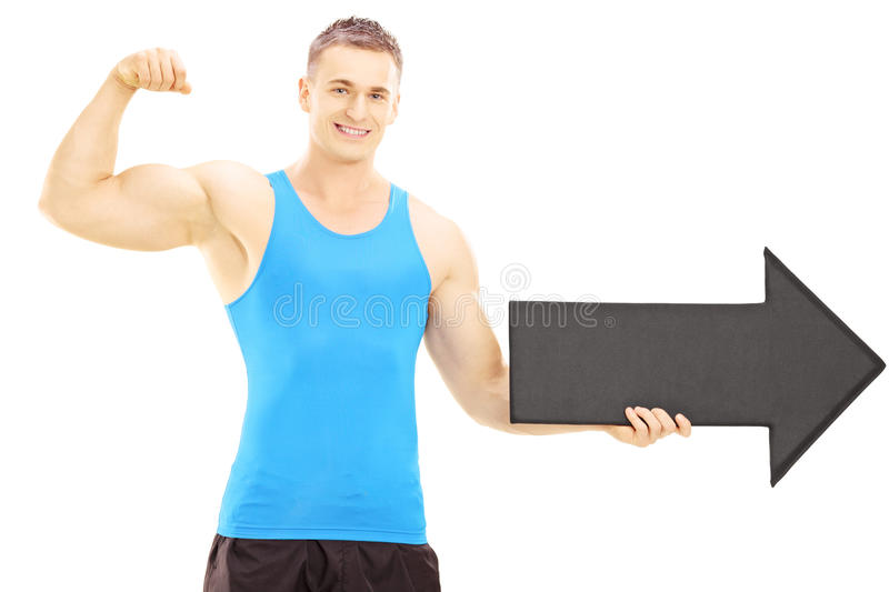 Muscular athlete showing his muscles and holding an arrow pointing right royalty free stock photo