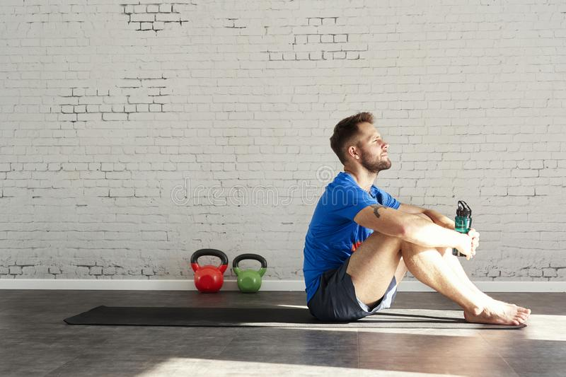 Muscular athlete sitting in sunny sport club, relaxed after workout, bottle of water in hands. Space for text layout on brick wall.  stock image