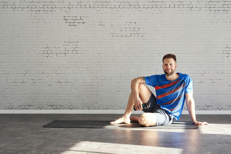 Muscular athlete sitting in sunny sport club, relaxed after workout, bottle of water in hands. Space for text layout on brick wall. Muscular handsome man athlete stock images