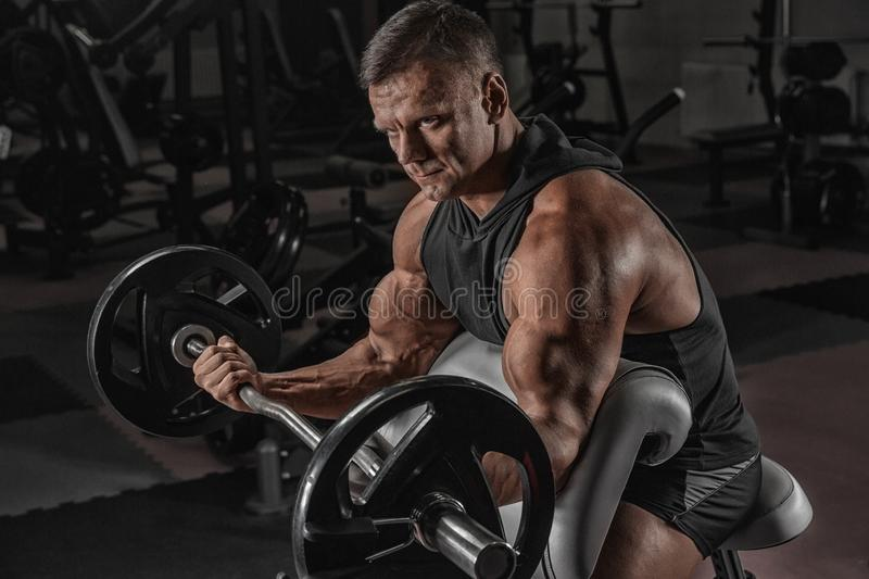 Muscular athletic bodybuilder fitness model posing after exercises in gym stock images