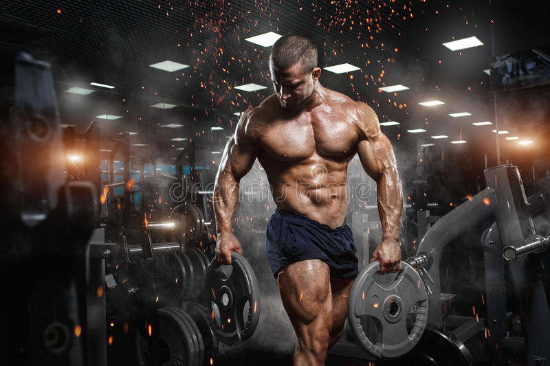 Muscular athletic bodybuilder fitness model posing after exercises in gym stock image