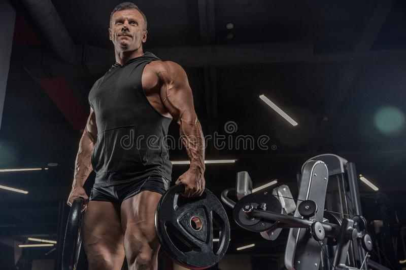 Handsome man with big muscles trains in the gym, exercises stock images