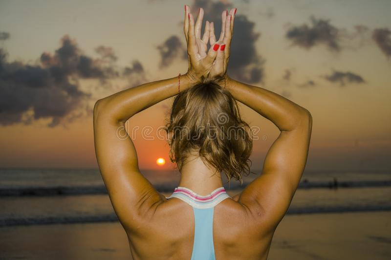 Muscular back of fit and healthy attractive woman practicing fitness and yoga in beautiful sunset beach in meditation and relaxati. On under amazing orange sky royalty free stock image