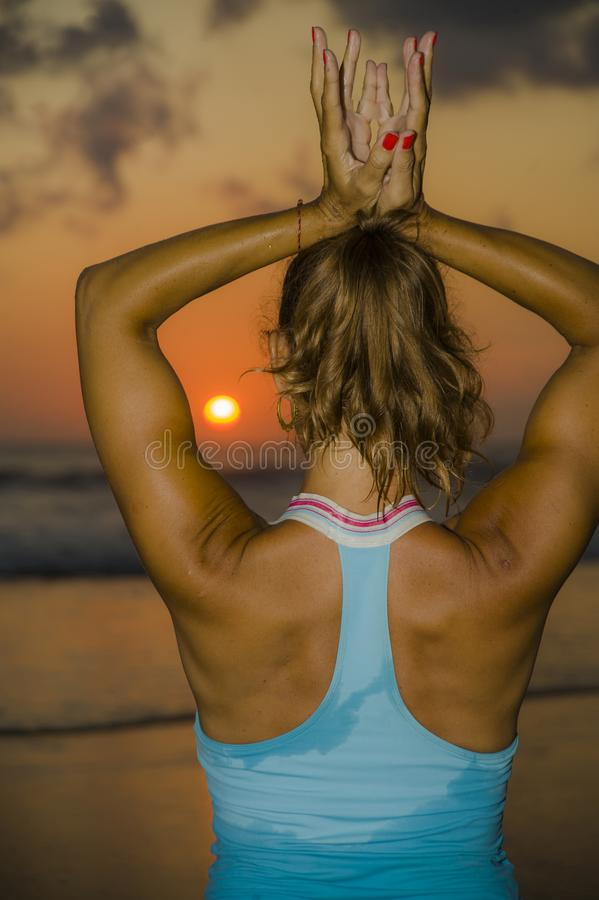 Muscular back of fit and healthy attractive woman practicing fitness and yoga in beautiful sunset beach in meditation and relaxati. On under amazing orange sky stock photography