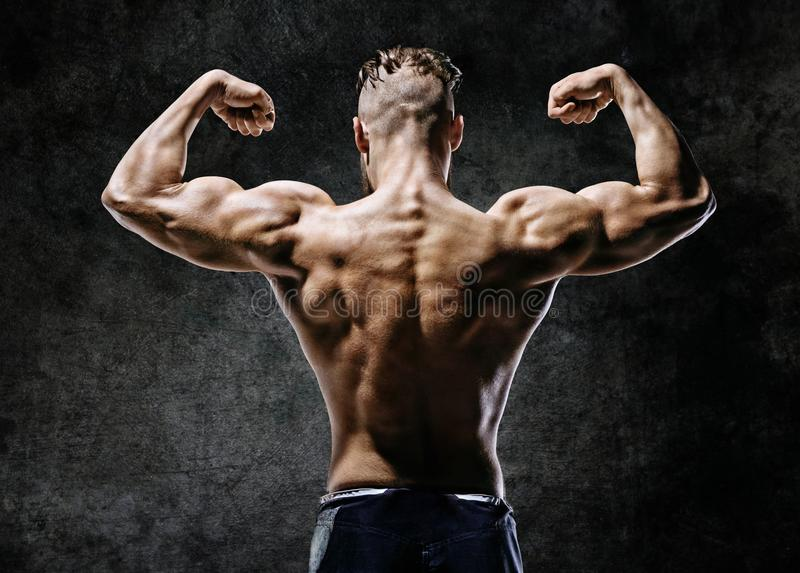 Muscular back of man flexing his arms. stock photo