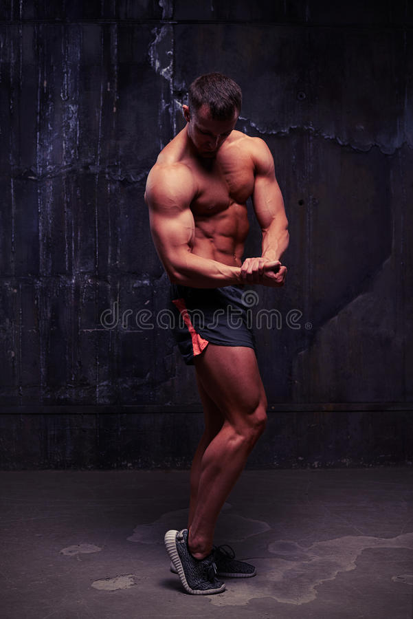 Muscular bare-chested man in sport shorts in studio against dark stock images