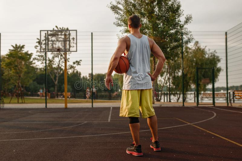 Muscular basketball player on outdoor court. Male athlete in sportswear holds ball on streetball training royalty free stock photos