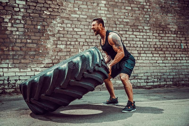 Muscular fitness man moving large tire. royalty free stock photography