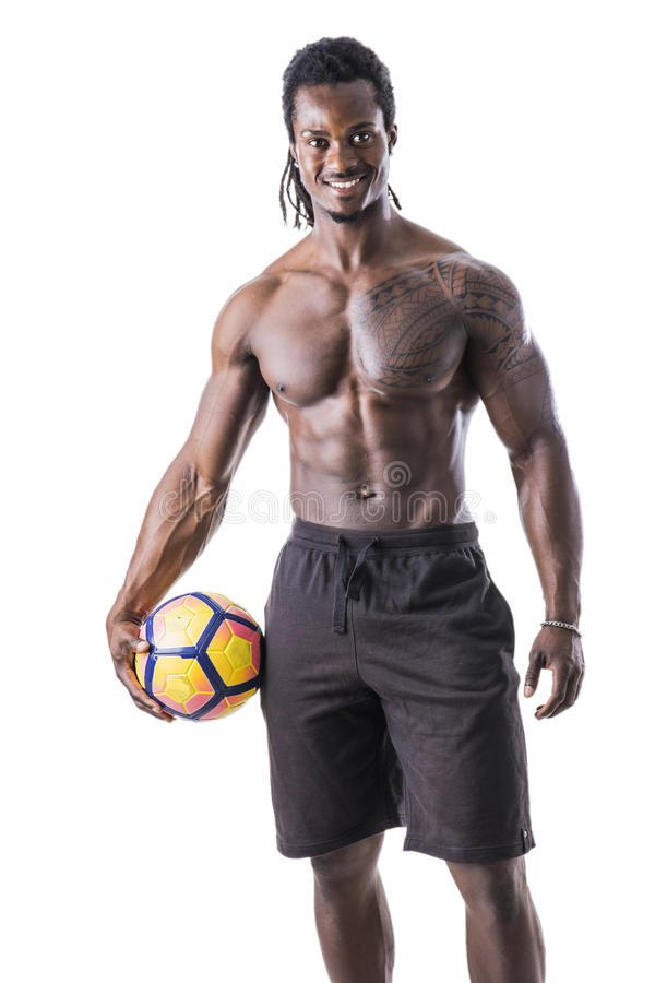 Muscular black man exercising with soccer ball royalty free stock photo