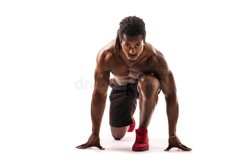 Muscular black man ready to sprint and run. Muscular shirtless handsome young black man ready to sprint and run in studio shot, isolated on white royalty free stock photography