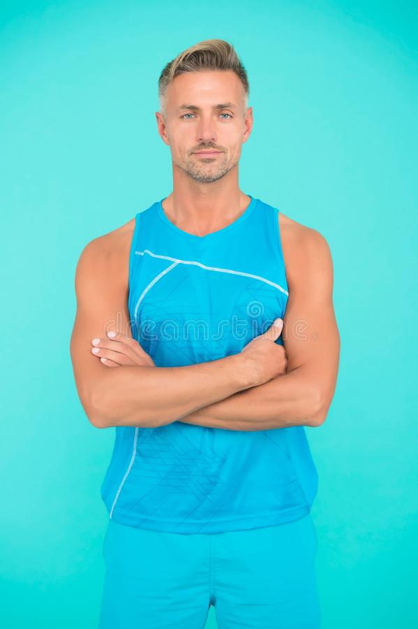 Muscular body. Man well groomed athlete on blue background. Mature but still in good shape. Exercising in gym for better stock photo