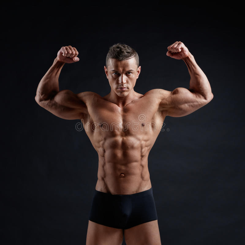 Muscular body. Young muscular bodybuilder posing over black background stock images